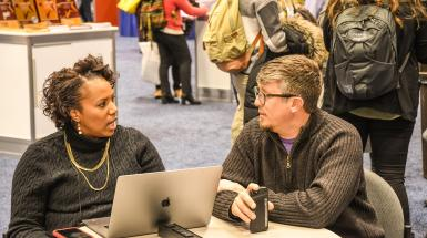 Man woman connecting talking at a table at Convention